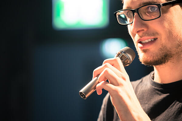 man talking in microphone - JConnelly Blog - Tech Entrepreneurs Be the Face of Your Brand