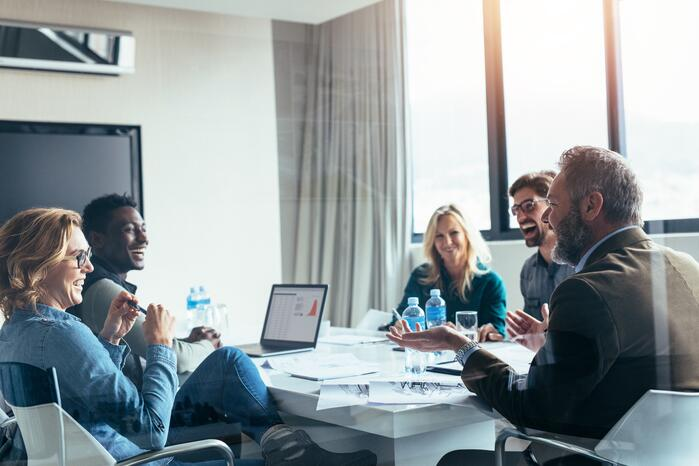 Employees smiling during a meeting- JConnelly Blog - Why a Smile Is Vital to Your Message